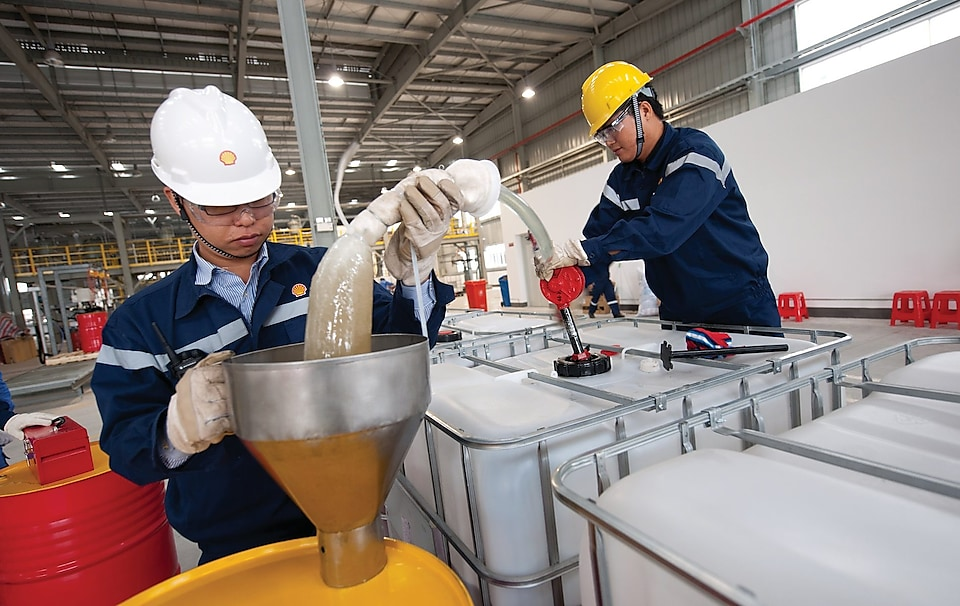 two workers busy in work concentrating over lubricants transferring