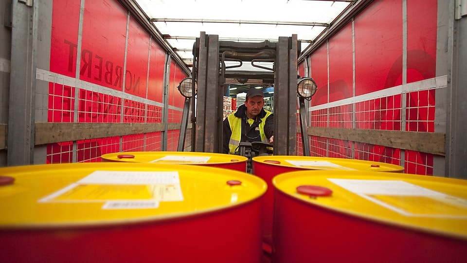 Truck Load driver loading the lubricants drums