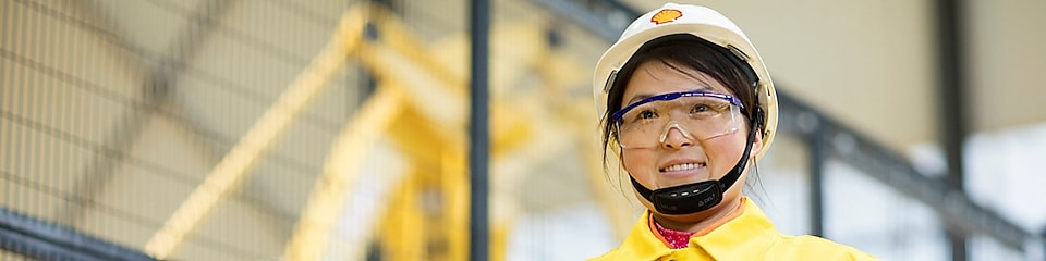 shell employee holding a remote control with a smile on her face