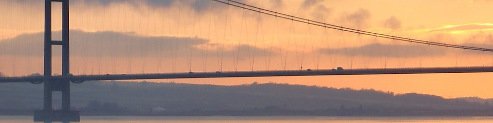 a suspension bridge over a river at sunset
