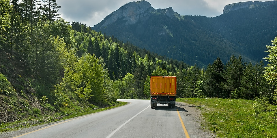 An orange truck driving in the mountains of Turkey.
