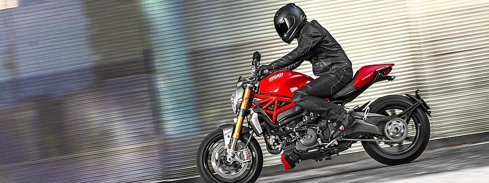A person fully dressed in black with a black helmet riding a ducati bike