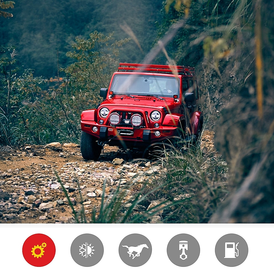 Image of a red jeep driving on an arid sandy off road track