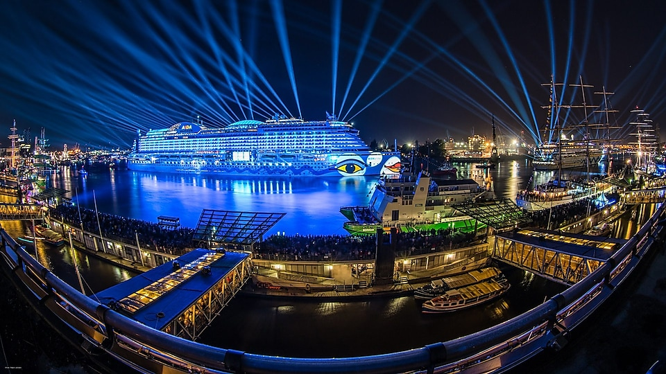 The AidaPrima lit up with blue lights and docked in Hamburg port at night
